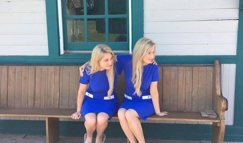Briana and Brittany wait for a train at a station.