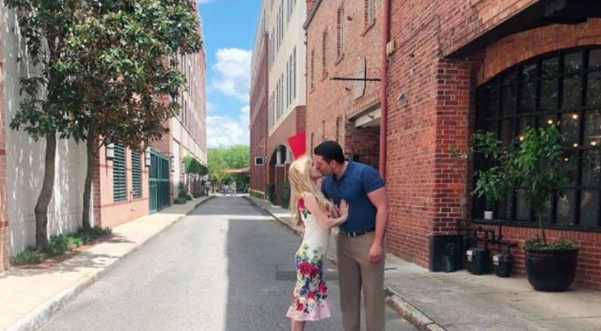 Jeremy and Briana kiss on a street in Charleston.