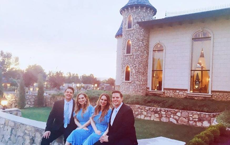 The twin Salyer couples sit in front of a stone castle.