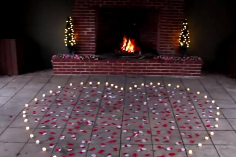 A heart made of flower petals and candles sits in front of a fireplace.