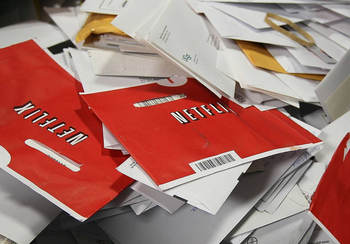 Red Netflix envelopes sit in a bin of mail.