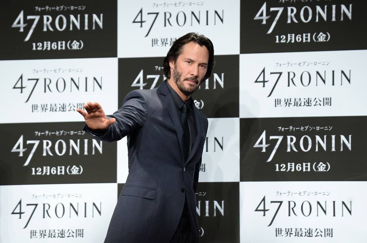 Keanu Reeves waves to journalists at a press conference for the movie 47 Ronin.