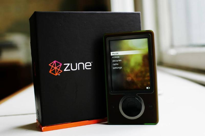 The Microsoft Zune MP3 player stands next to the box.