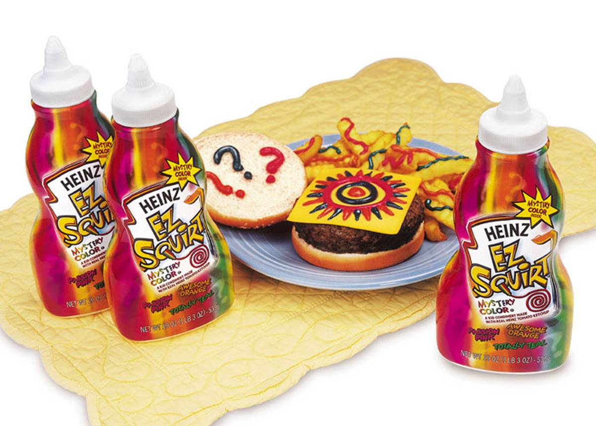 Heinz ketchup, in multi colored squirt bottles, are displayed with decorated fries.