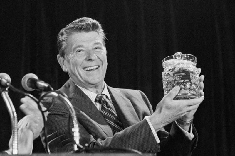 Ronald Reagan holds up a glass container of jelly beans.