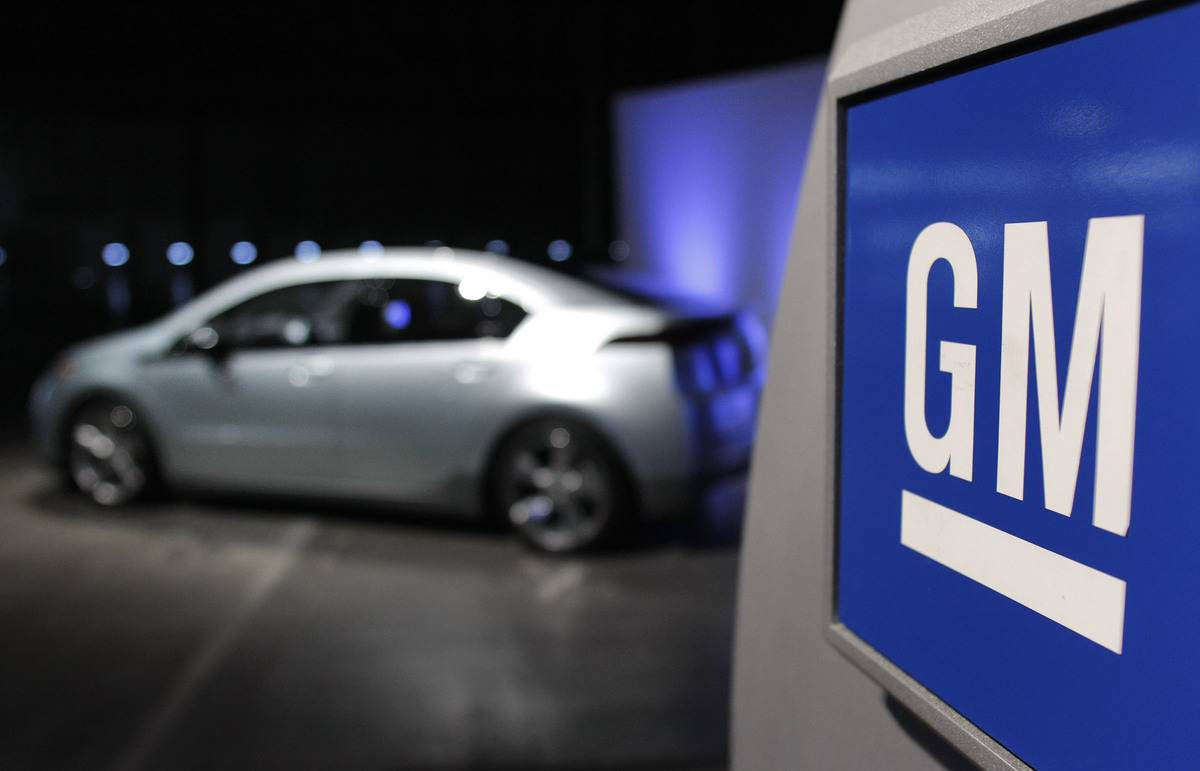 The General Motors logo is pictured in front of a car.