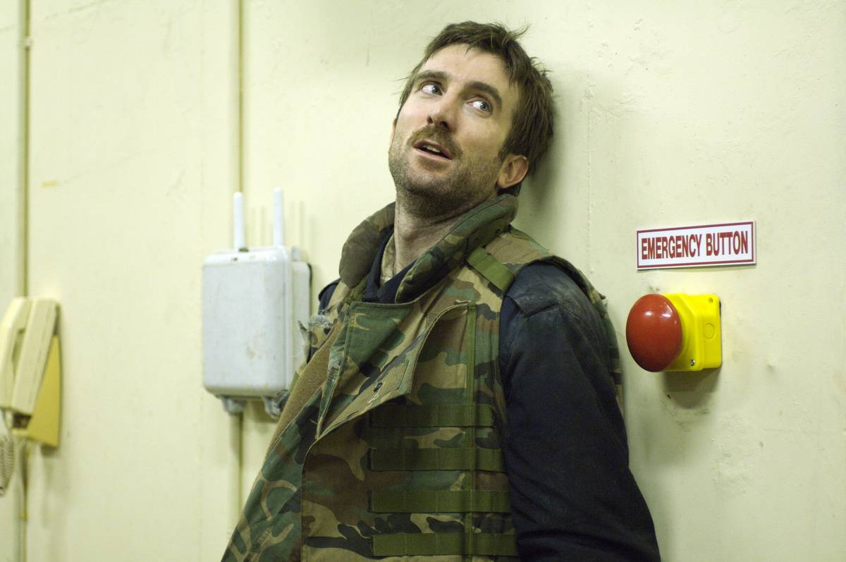 a man wearing a camo vest in district 9