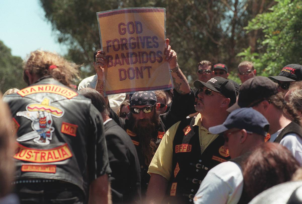 A member of the Bandidos motorcycle club holds up a sign that says,