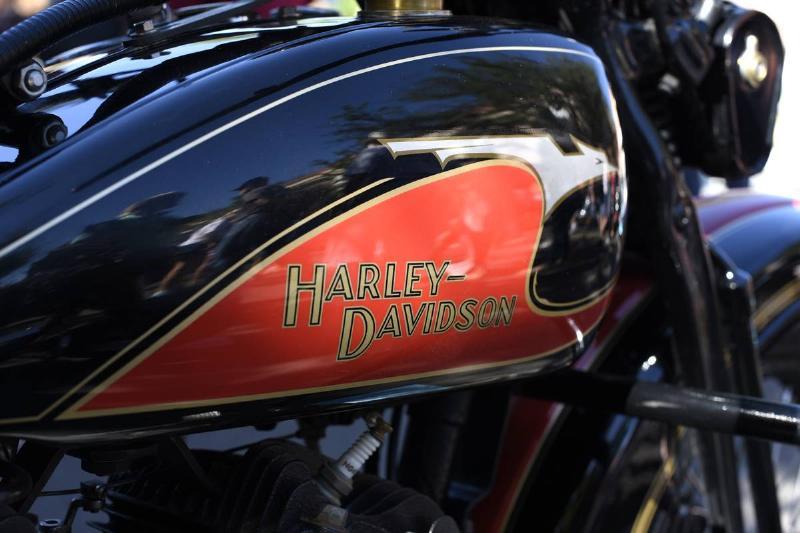 A close-up of a motorcycle shows a Harley Davidson logo.