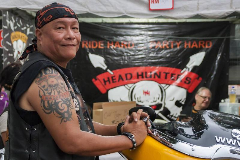A biker from the motorcycle club Head Hunters is seen in front of a flag.