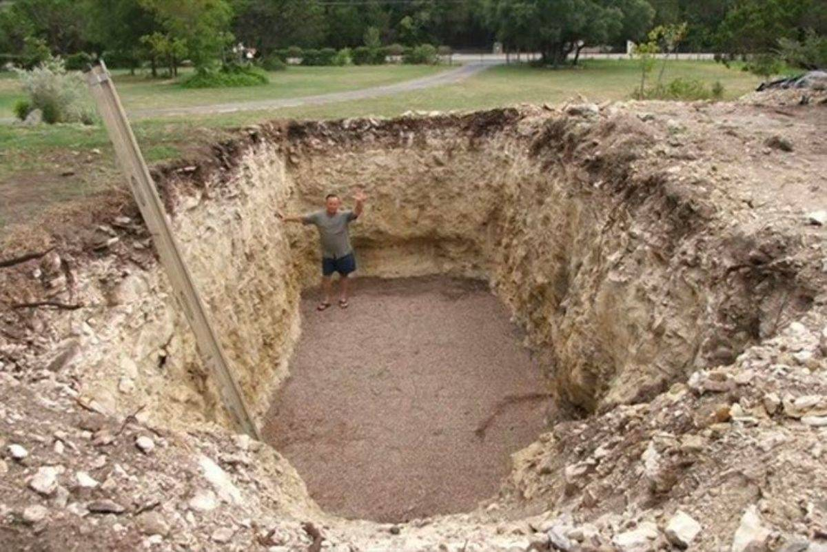 A man stands in a giant hole that he dug in his backyard.