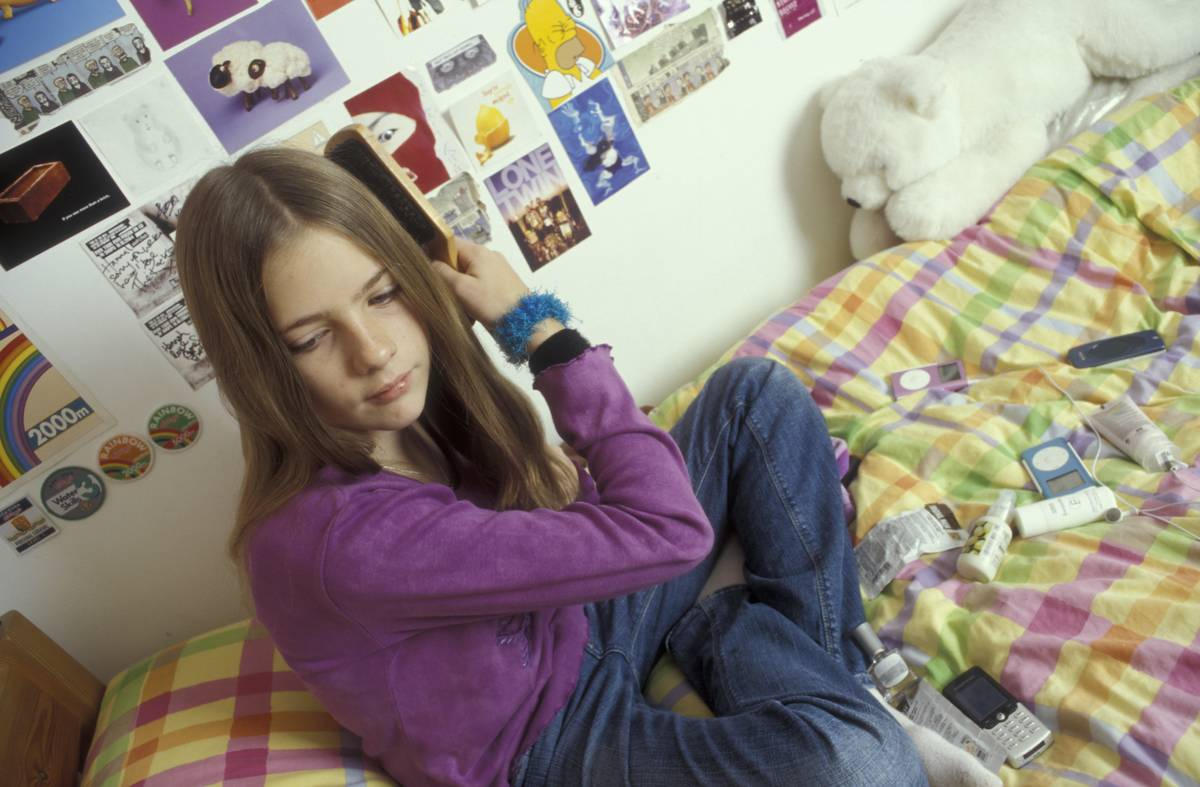 A teenage girl brushes her hair while sitting on her bed.