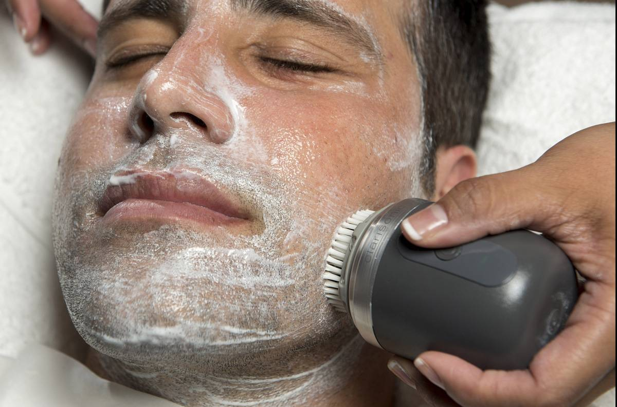 A salon owner uses a brush to exfoliate a man's face.