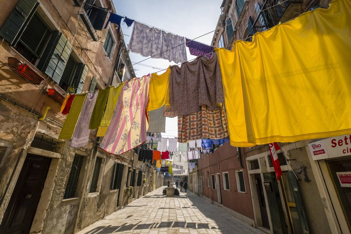 Colorful clothes hang from clotheslines on a narrow street.