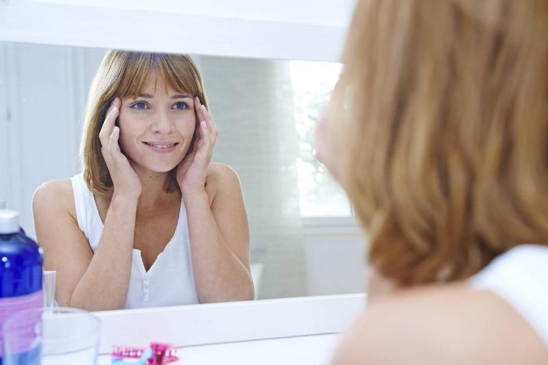 A woman looks at her face in the mirror.