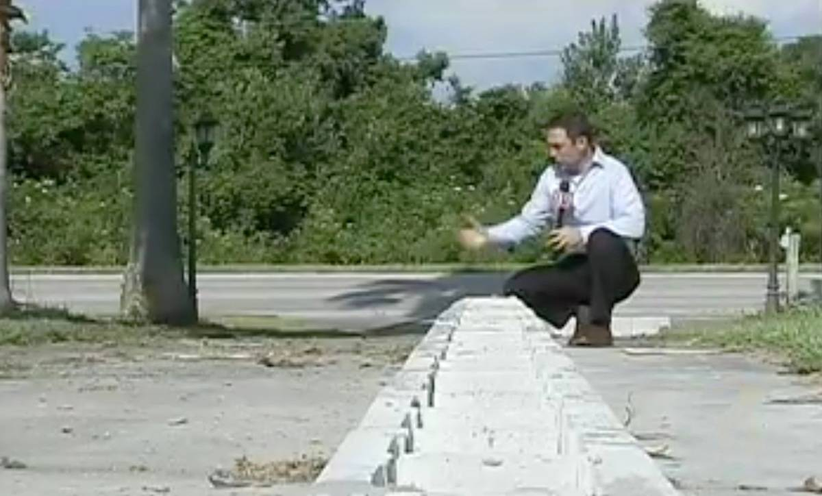 A reporter looks at the row of cinder blocks and comments.
