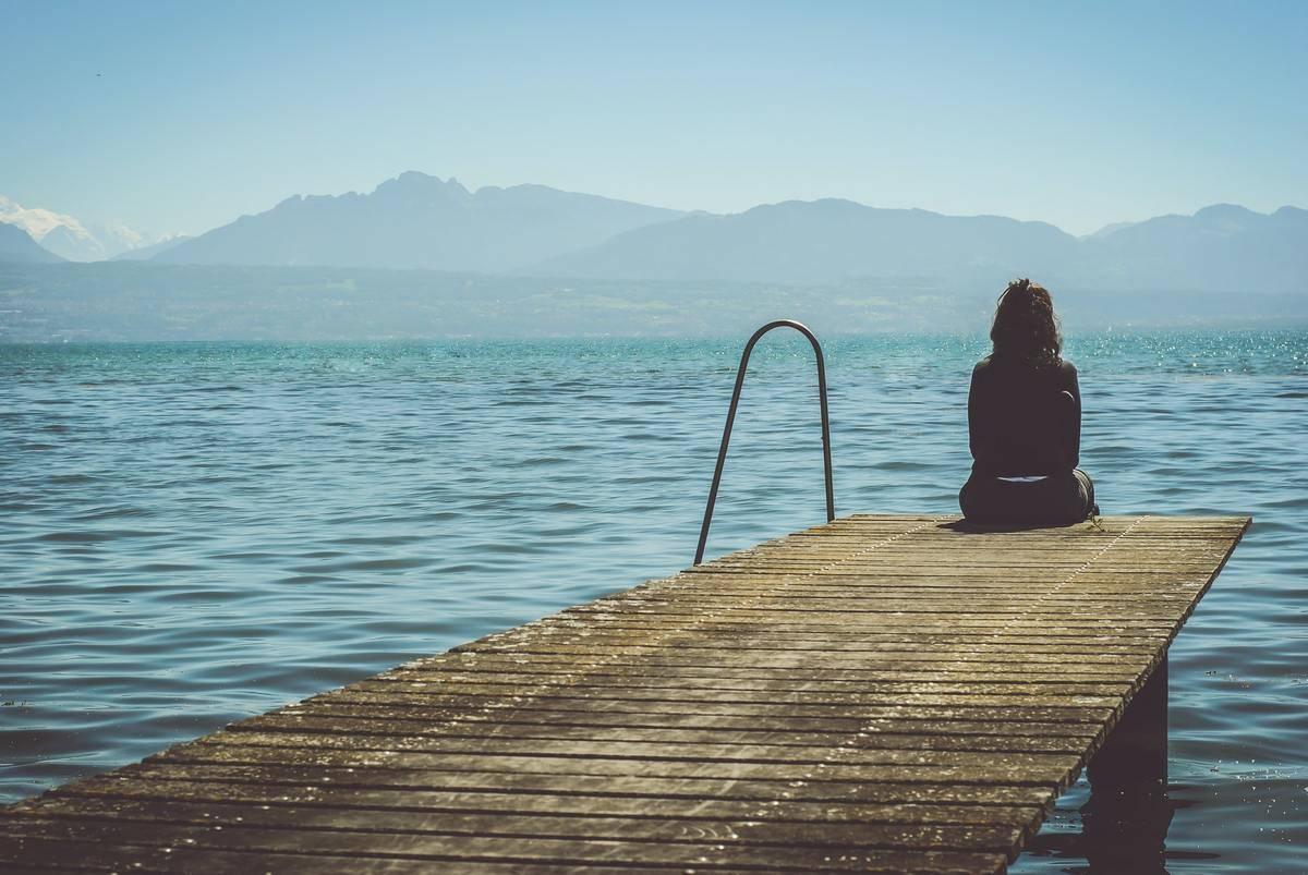A woman stars at a lake forlornly.