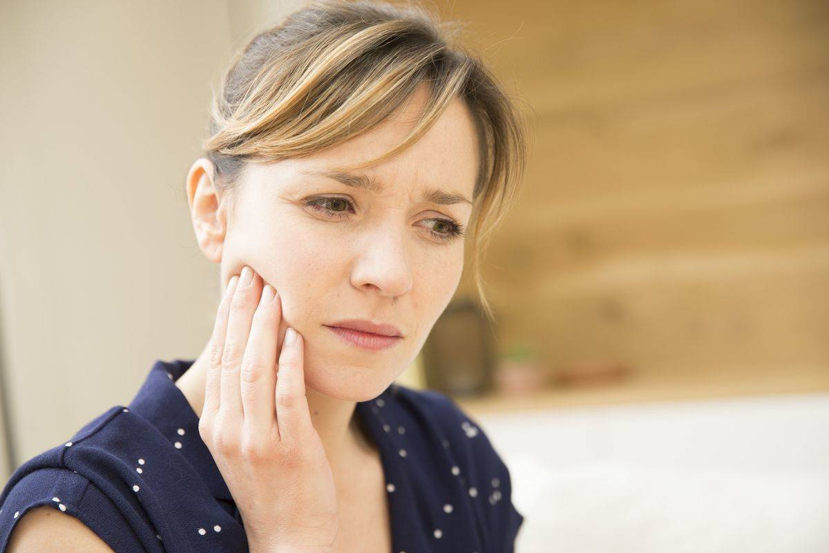 A woman touches her jaw because of a painful toothache.