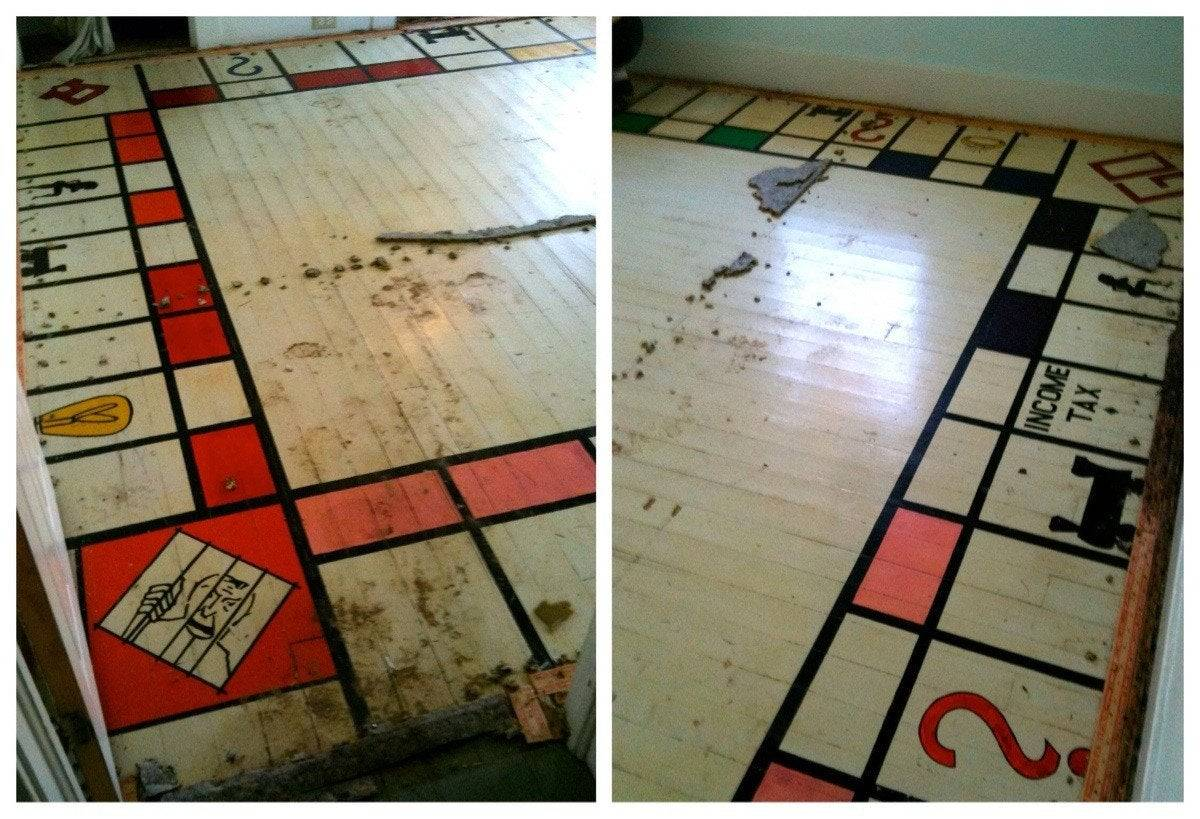 A giant risque Monopoly board is seen underneath a carpet.