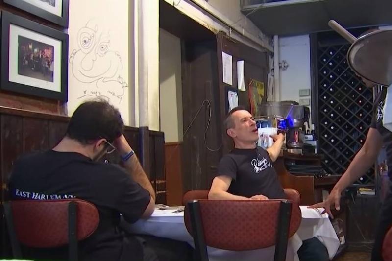 Waiter Armando Markaj sits with his boss, Frank Brija, as he speaks to another waiter.