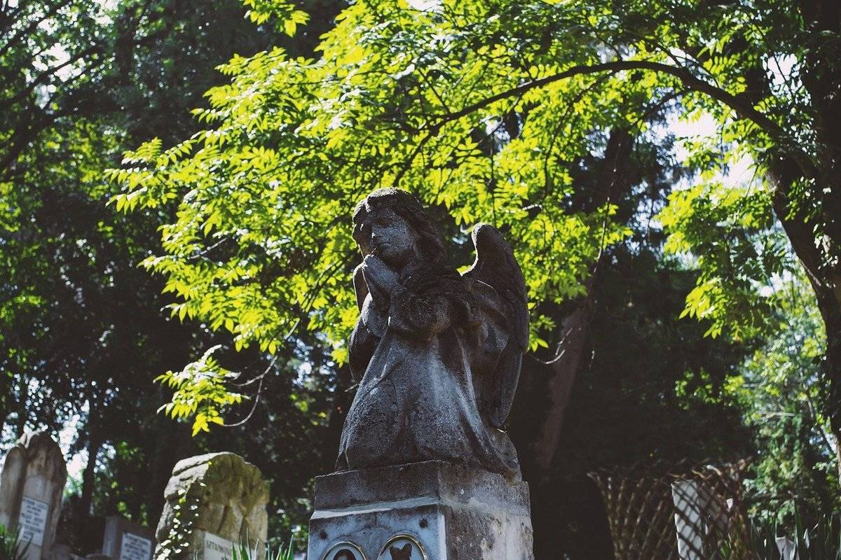 A child's headstone includes an angel statue.