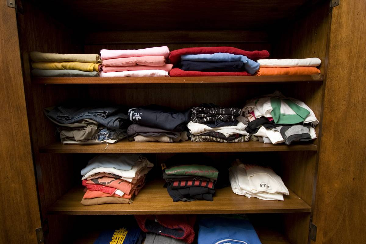 A closet is filled with folded shirts.