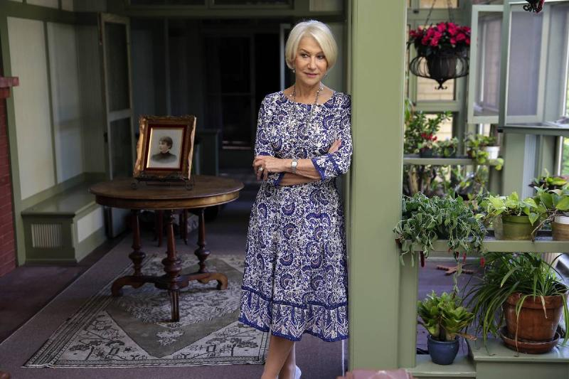 Actress Helen Mirren stands in the Winchester mansion next to furniture and a portrait of Sarah Winchester.