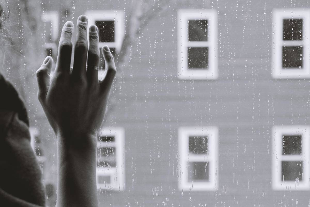 A woman holds her hand up to a window with rain outside.