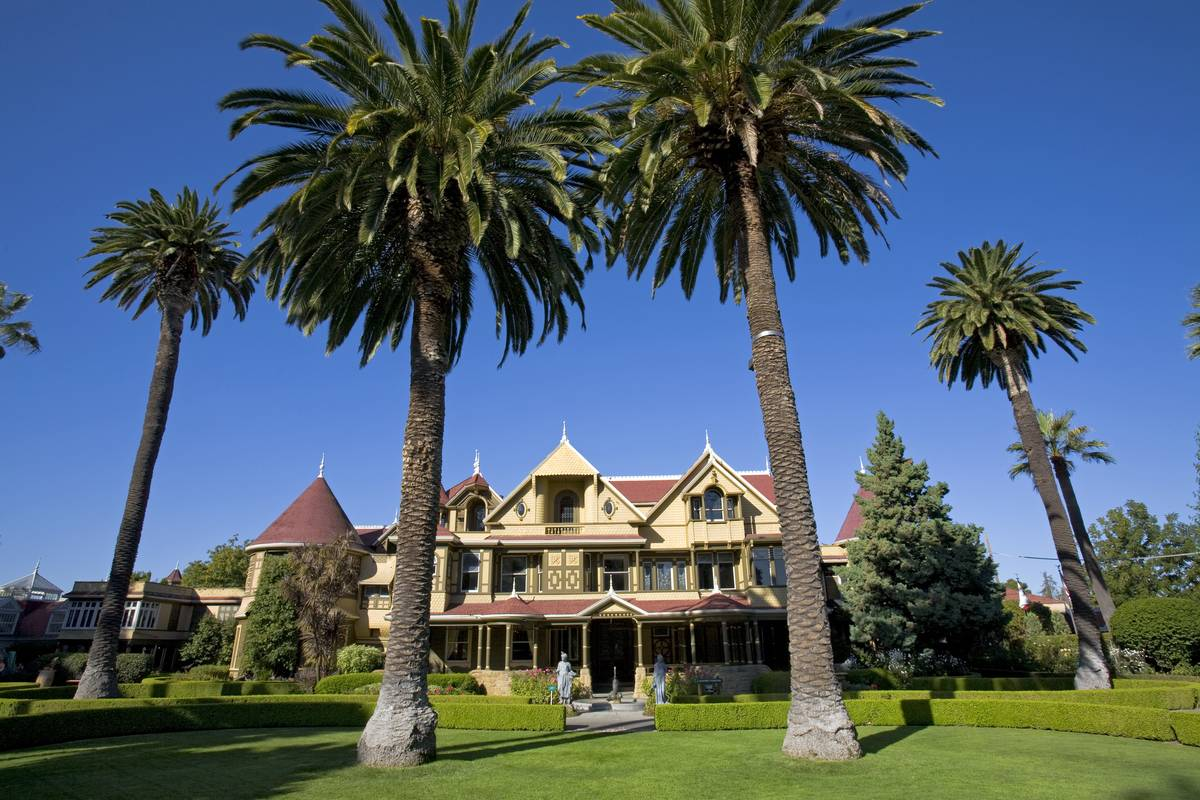 Palm trees grow around the Winchester Mystery House.