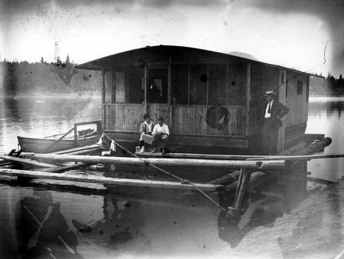A photo shows a couple on a houseboat in the early 1900s.