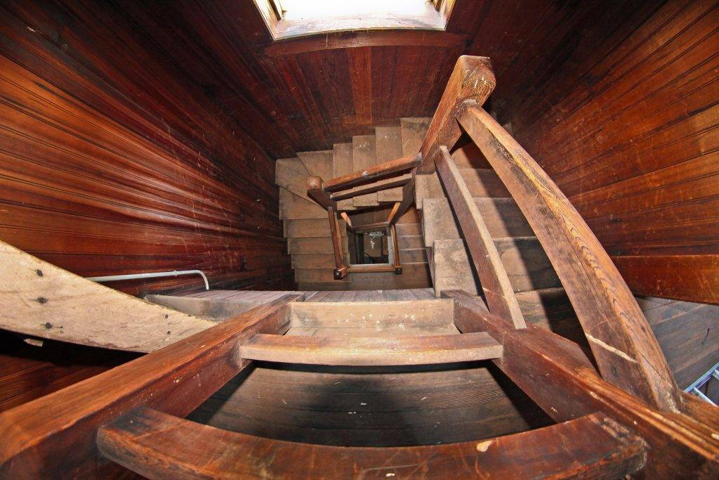 A view from the top of a spiral staircase in the Winchester Mystery House looks down.