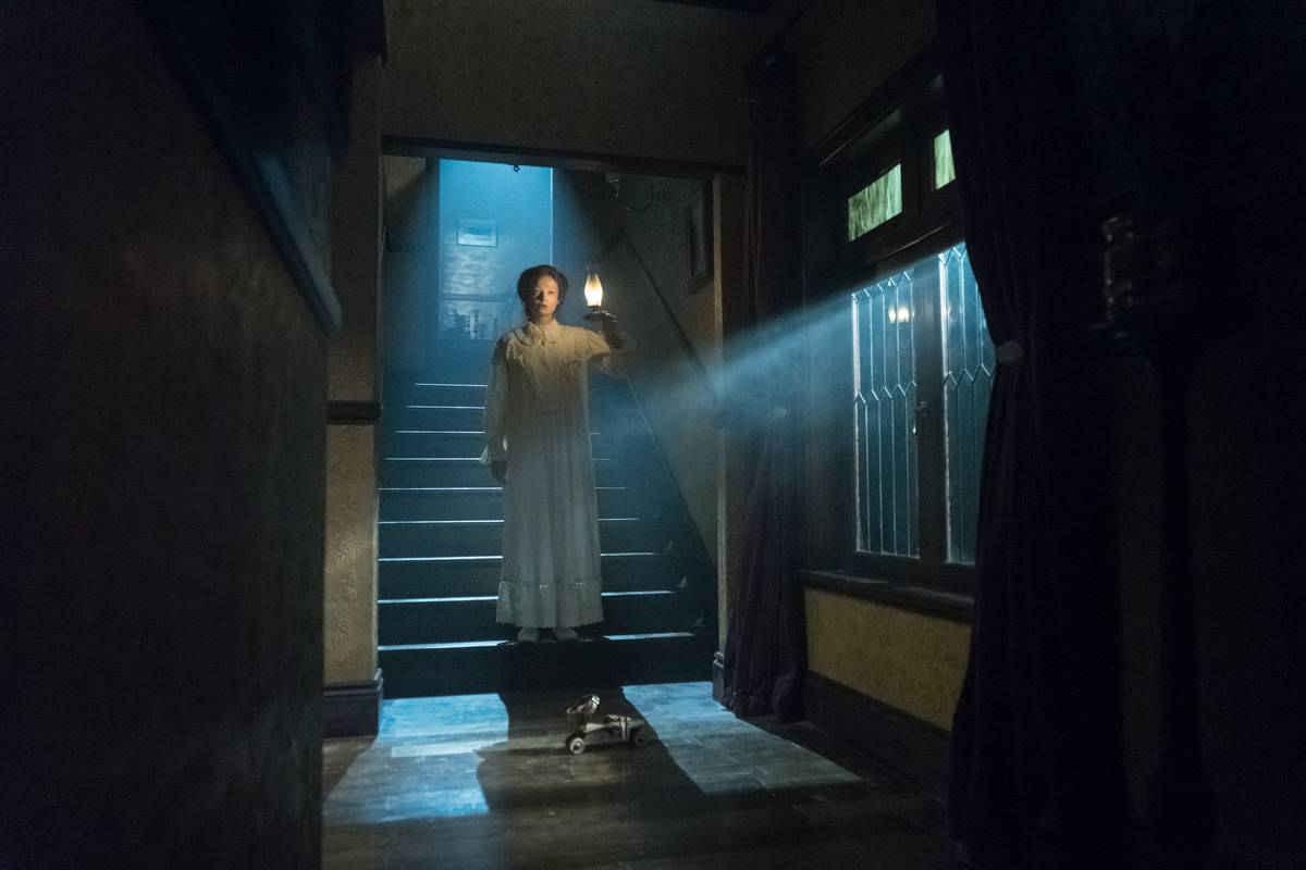 A still of the movie Winchester shows Sarah Snook standing in a hallway.