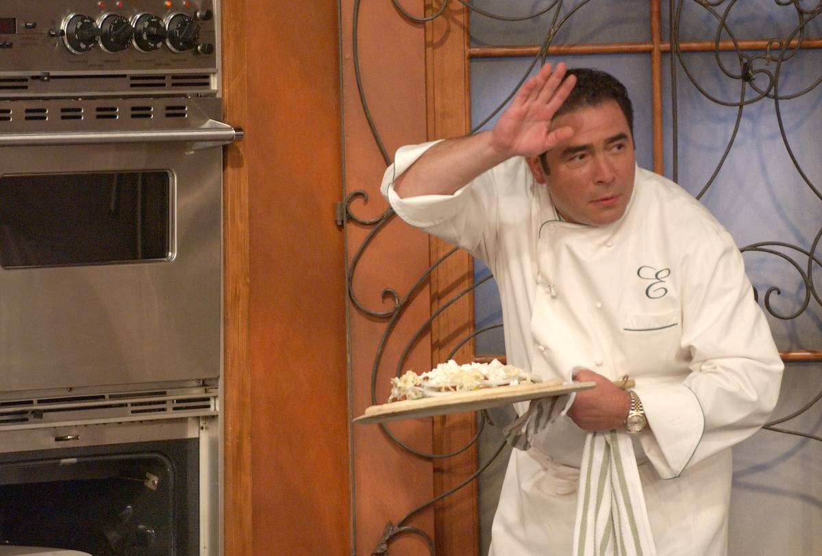 Emeril Lagasse prepares to put a dish into the oven on