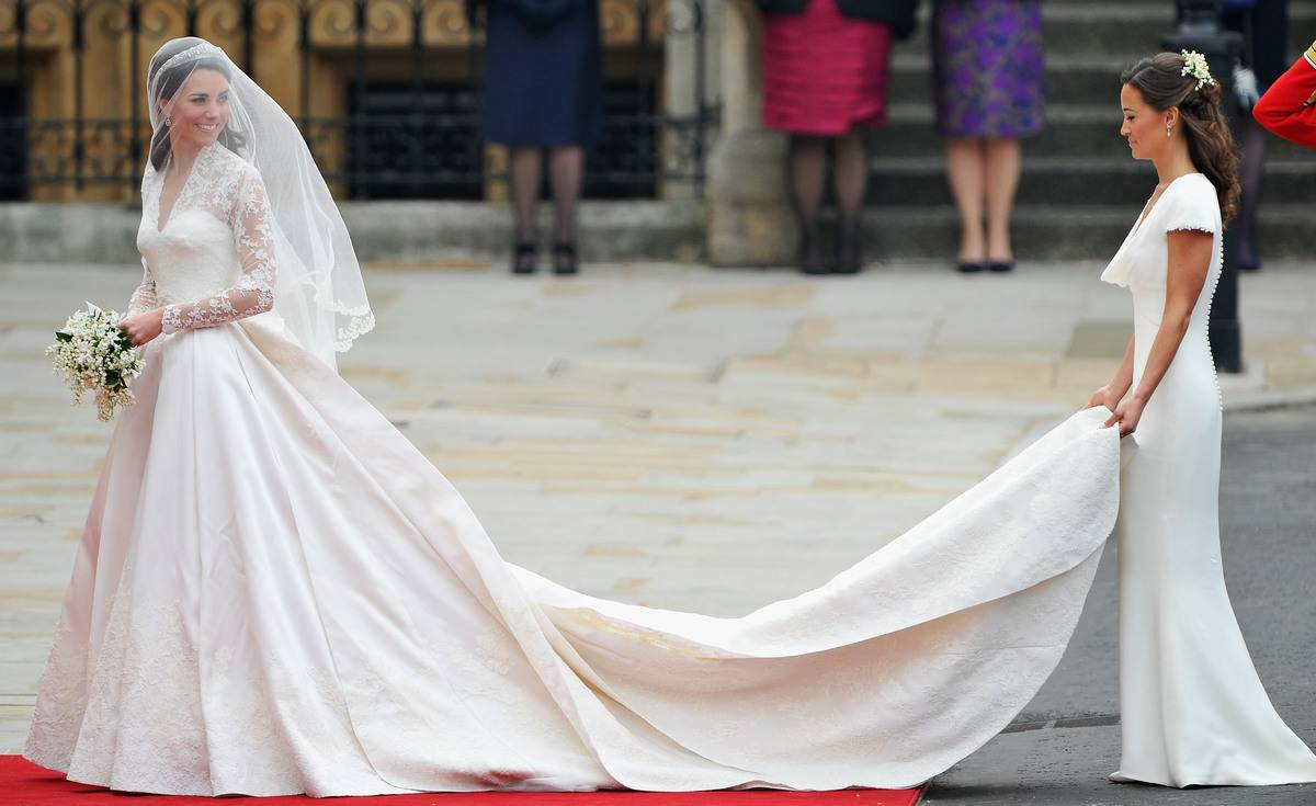 Catherine Middleton waves to the crowds as her sister and Maid of Honour Pippa Middleton holds her wedding dress.