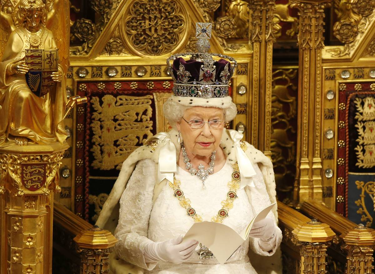 Queen Elizabeth sits on the throne during the opening of Parliament while wearing ceremonial robes and a crown.