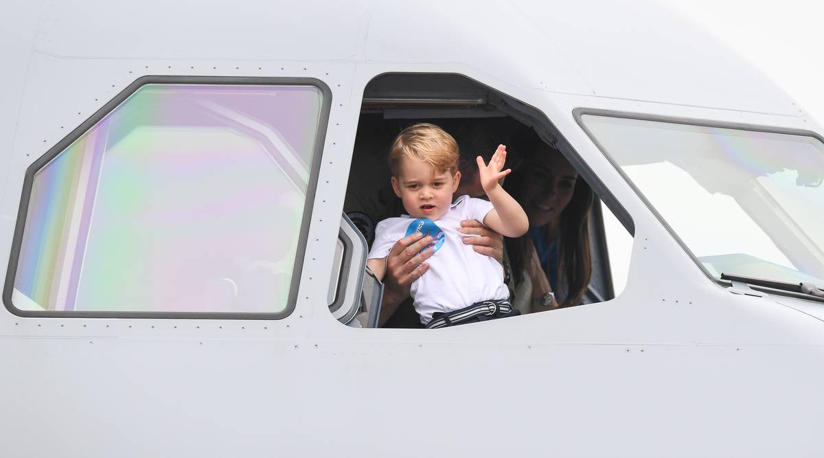 Prince George waves from the cockpit of an airplane.