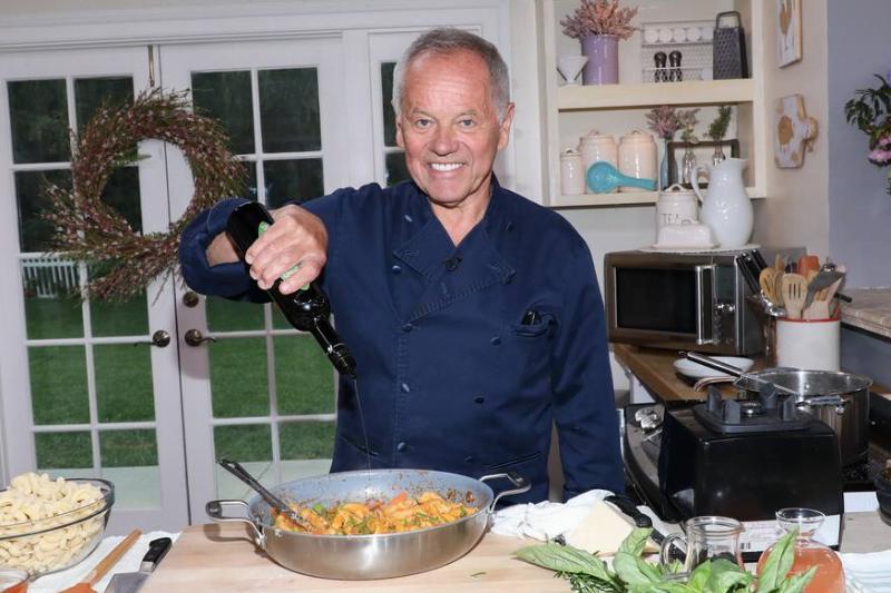 Wolfgang Puck mixes a salad dressing while smiling at the camera.