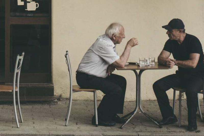 Two older men talk while sitting at a cafe table.