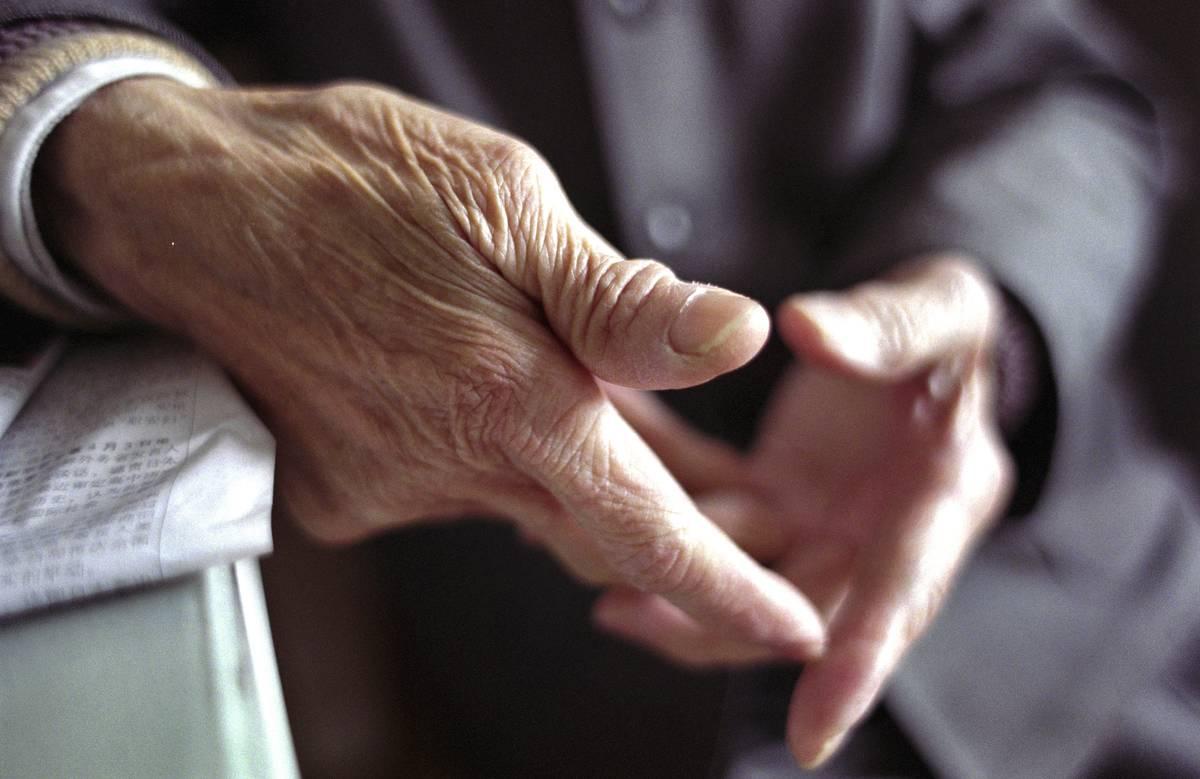 A close-up shot shows an elderly man's wrinkled hands.