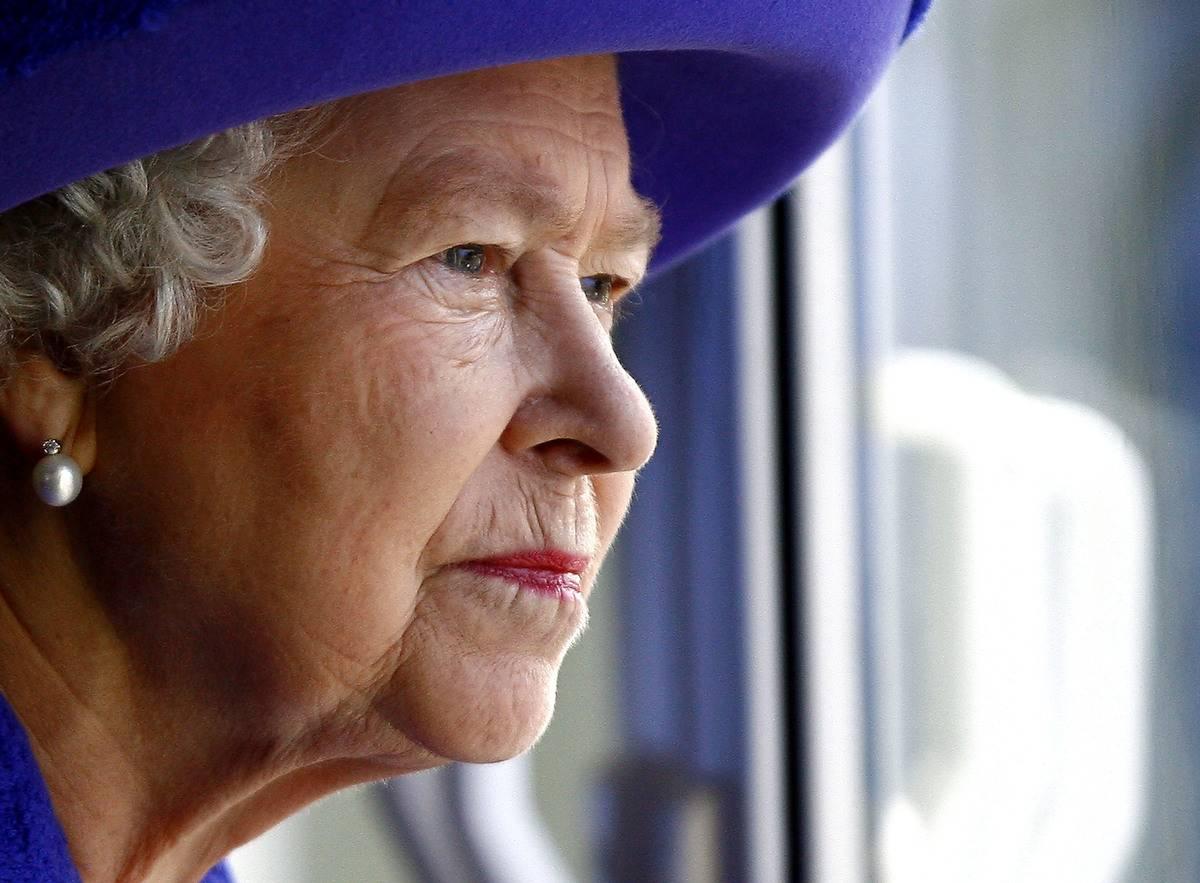 Queen Elizabeth II looks out from a window.