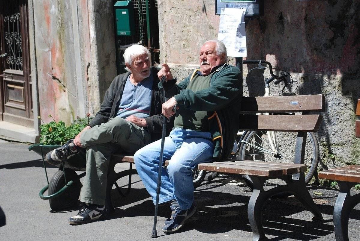 Two elderly men sitting on a bench argue.