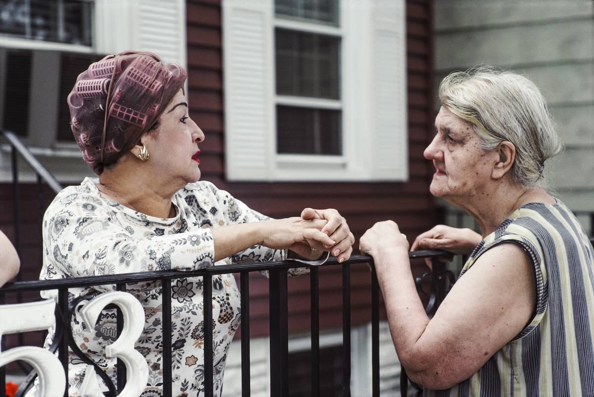 Two elderly neighbors chat over a fence.