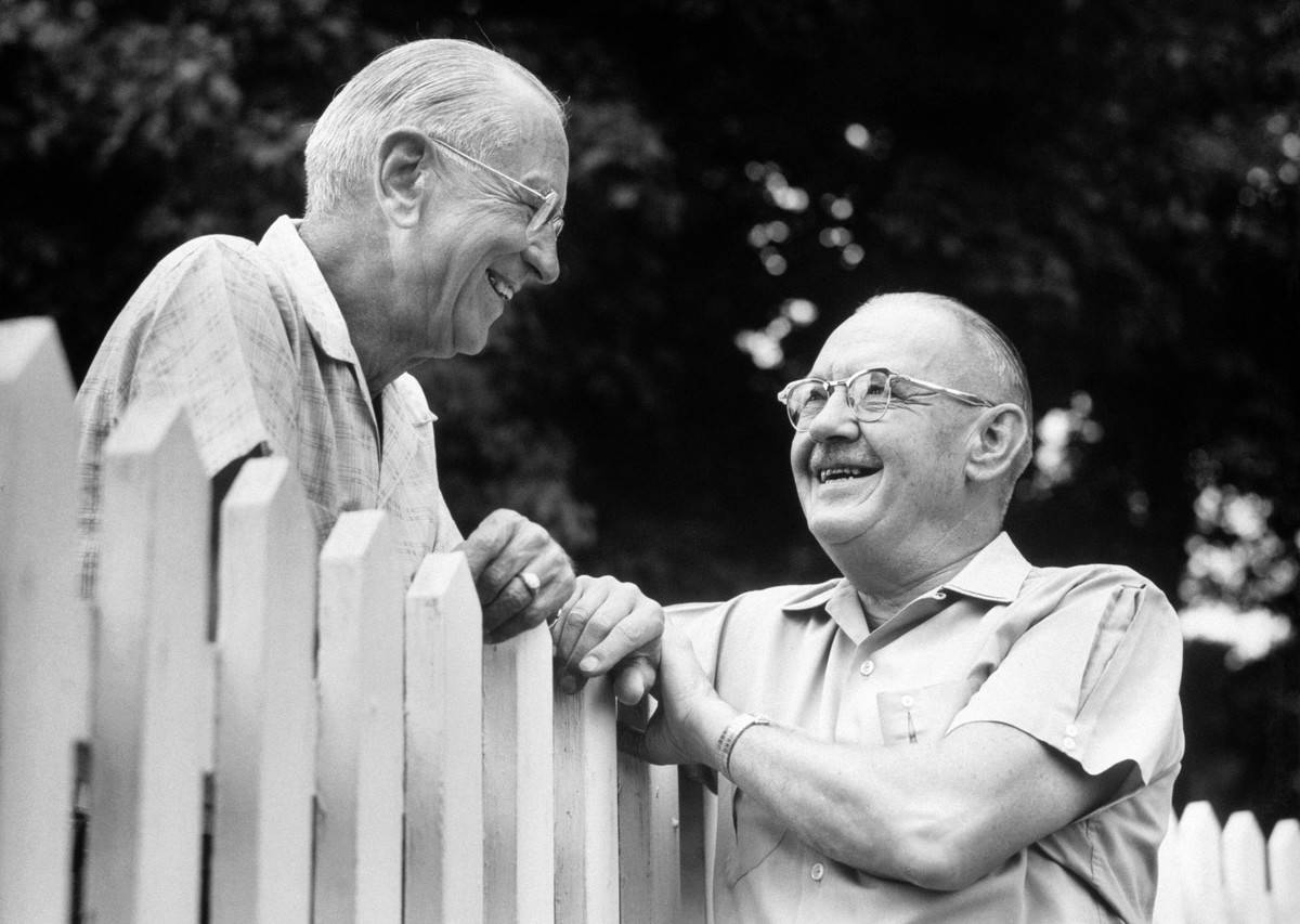 Two elderly men speak over a fence.