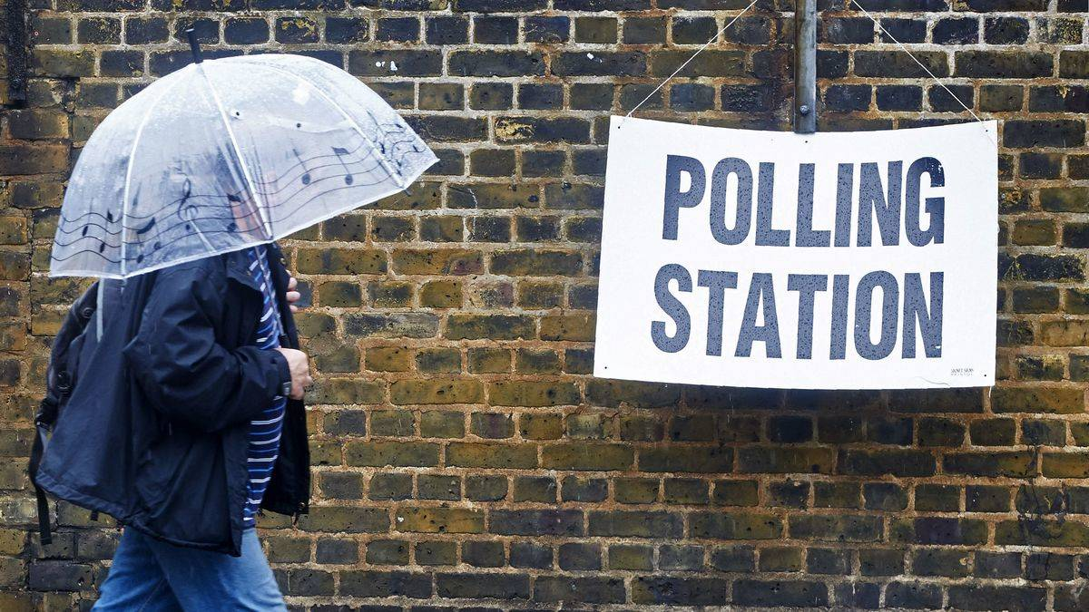 A person with an umbrella walks toward a polling station.