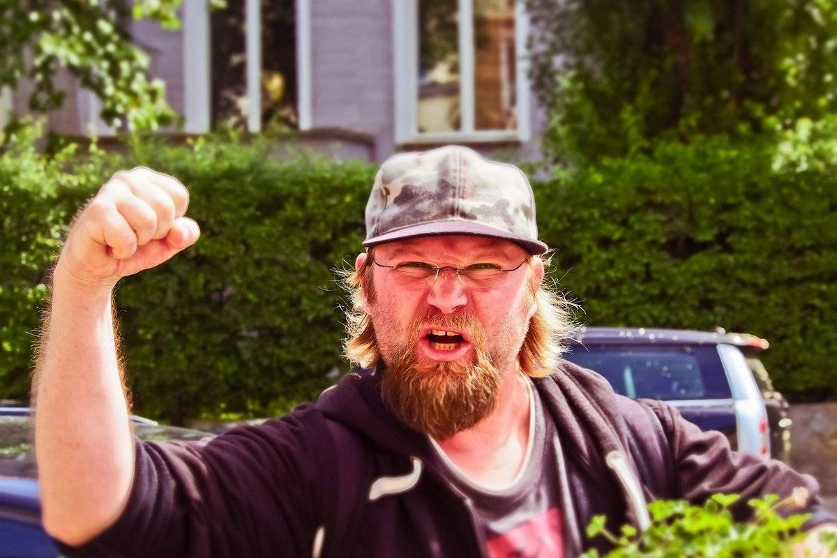 A neighbor yells and raises his fist at the camera.