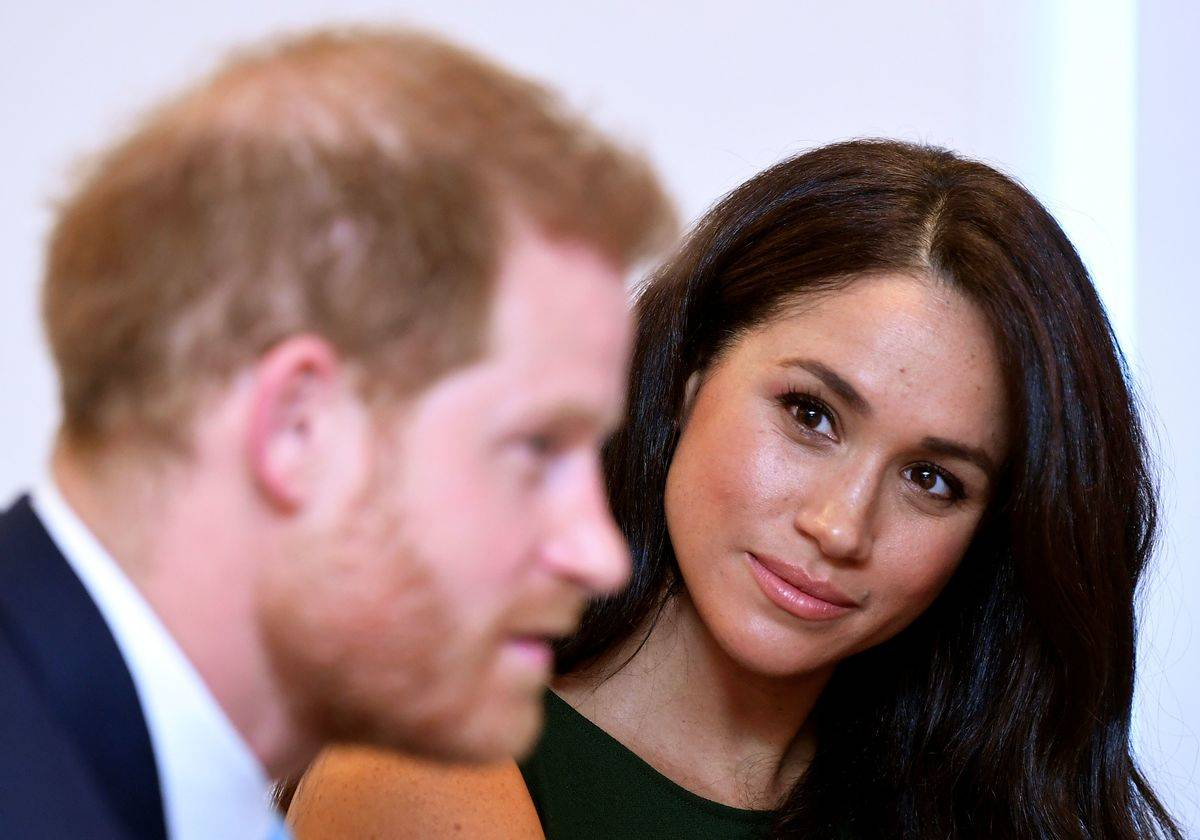 Meghan Markle looks at Prince Harry and listens as he speaks.