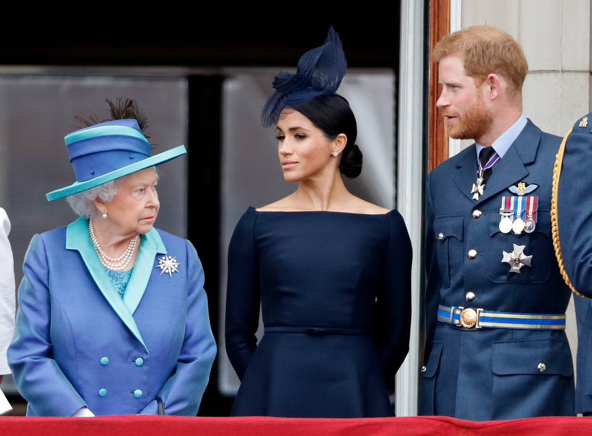 Harry and Meghan stand with the Queen as they watch the Royal Air Force.