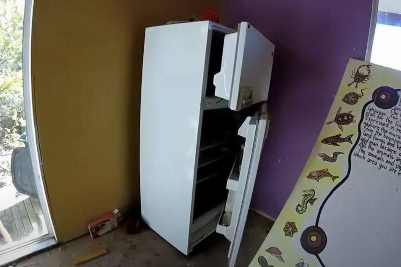 an open fridge next to a purple wall