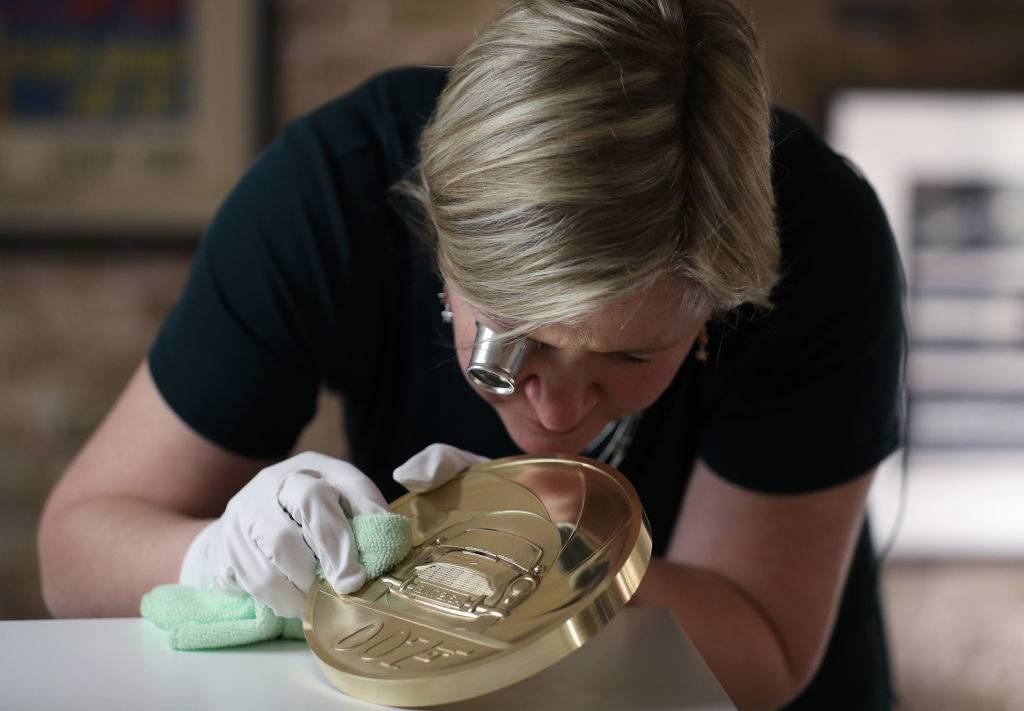 Royal Mint designer Laura Clancy, polishing a brass replica of a unique 7 kilo gold James Bond coin