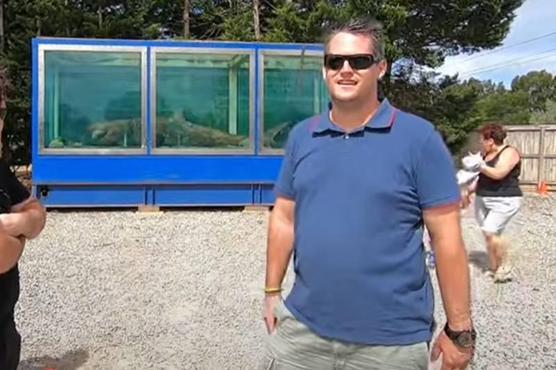 luke mcpherson posing in front of rosie the shark's tank